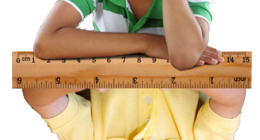 two children (one upside down) with a ruler in the middle