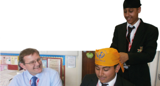 A secondary pupil putting a turban on another boy while the teacher watches