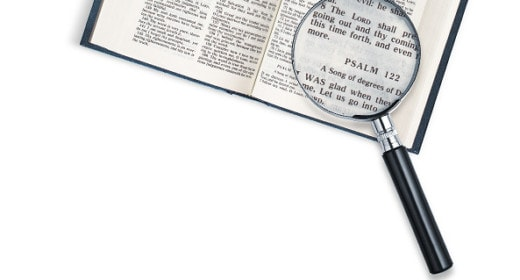 Bible with a magnifying glass