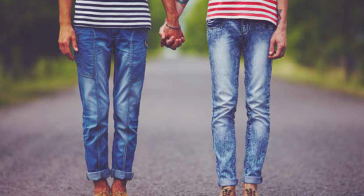 Showing the legs of 2 people standing in a road wearing bue jeans and brown shoes holding hands